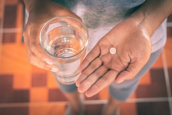 Close Up Of Girl holding Paracetamol and glass of water.