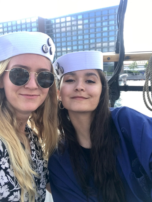 Two women in sailor's hats pose for a selfie on a sunny day in Copenhagen, Denmark.
