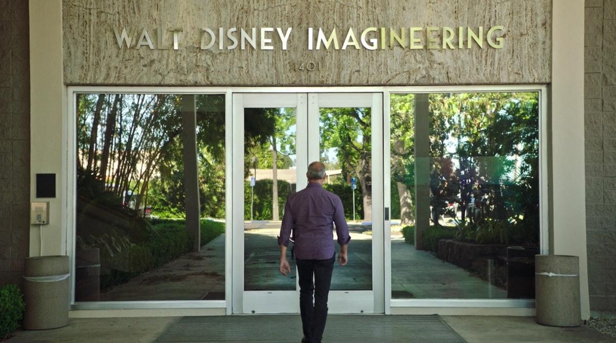 A man walks into the front doors of the Disney Imagineering building in California.