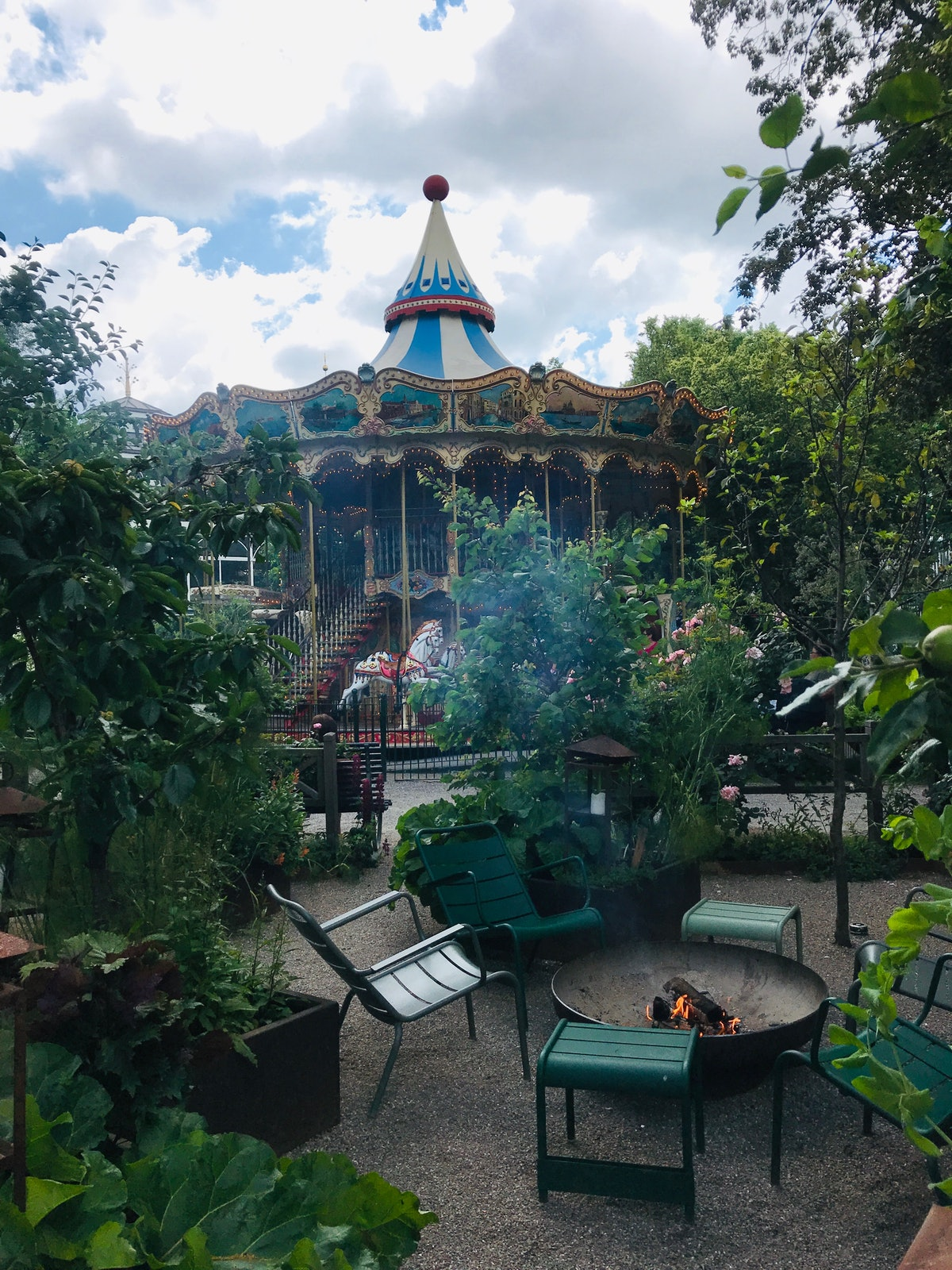 A beautiful carousel is surrounded by greenery at the Tivoli Gardens in Copenhagen, Denmark.