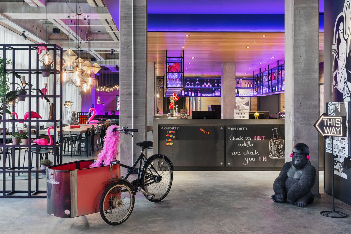 The interior of Moxy Copenhagen has pink flamingo decor and a cool bar with purple lights.