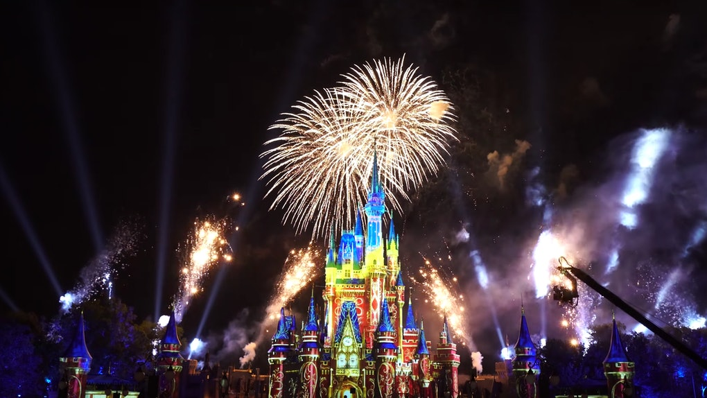 Fireworks light up the sky at night behind a lit up Cinderella castle at Disney World's Magic Kingdom.