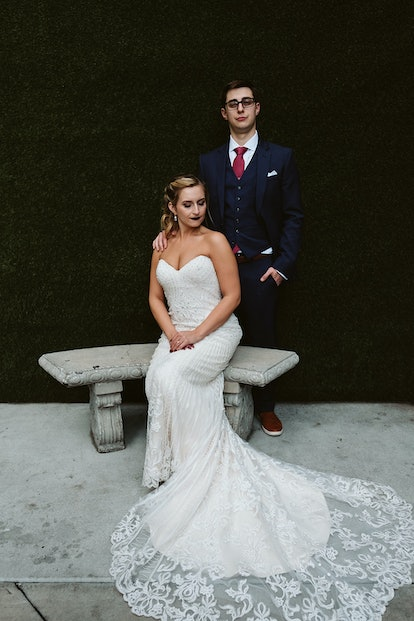 Rachel Varina in a Kitty Chen wedding gown poses on wedding day with husband in front of greenery wa...