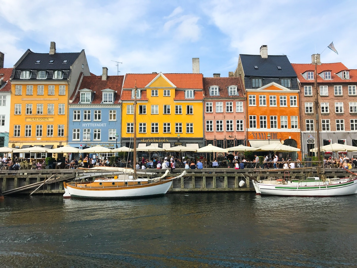 A row of colorful buildings overlooks a canal with boats in Copenhagen, Denmark.