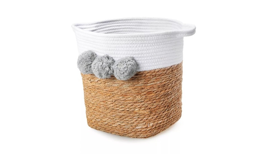 Basket with white across the top, three gray poms, and handles