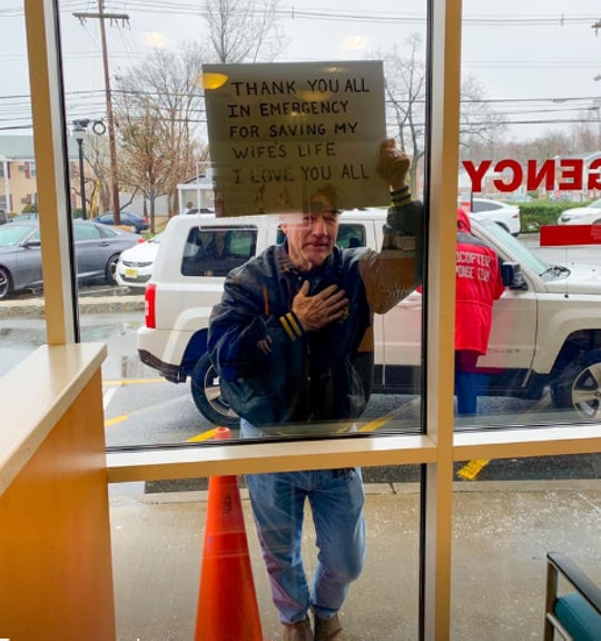 A man thanked healthcare workers for saving his wife by holding a sign up through a glass window.