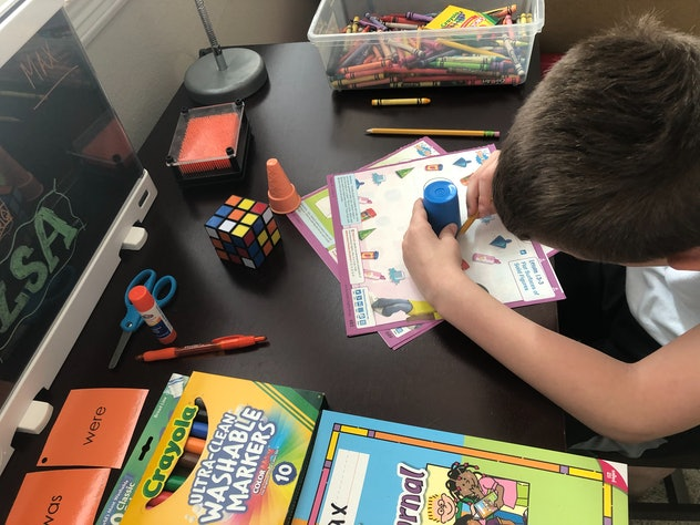 Working on school work is one way kids can entertain themselves while practicing social distancing a...