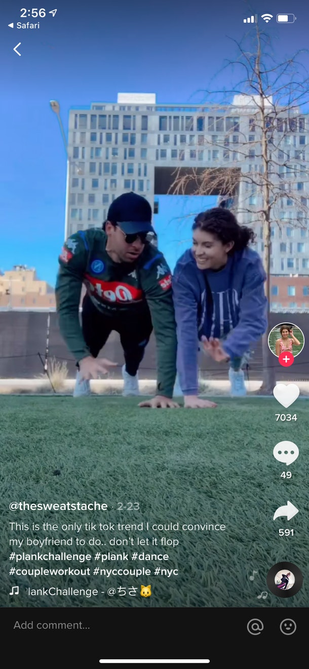 A young couple does the plank challenge from TikTok in a park.