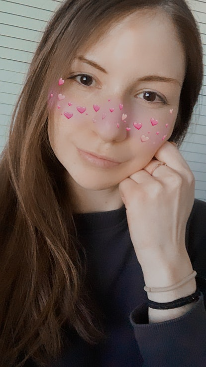 A young woman poses with an Instagram filter that puts hearts over your cheeks.
