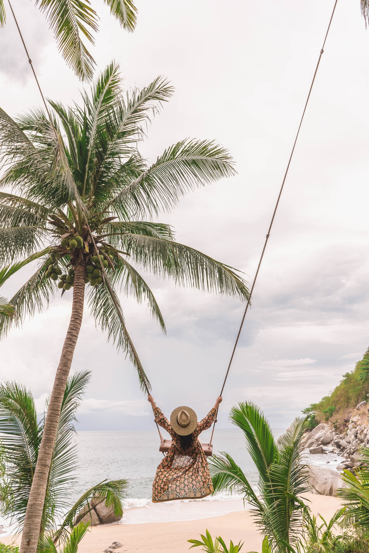 A woman in a flowy dress swings on a long rope swing in the middle of palm trees