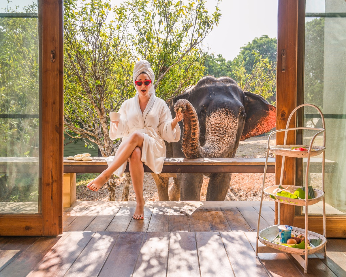 A woman in a bathrobe and towel around her hair sits on a porch with an elephant next to her.