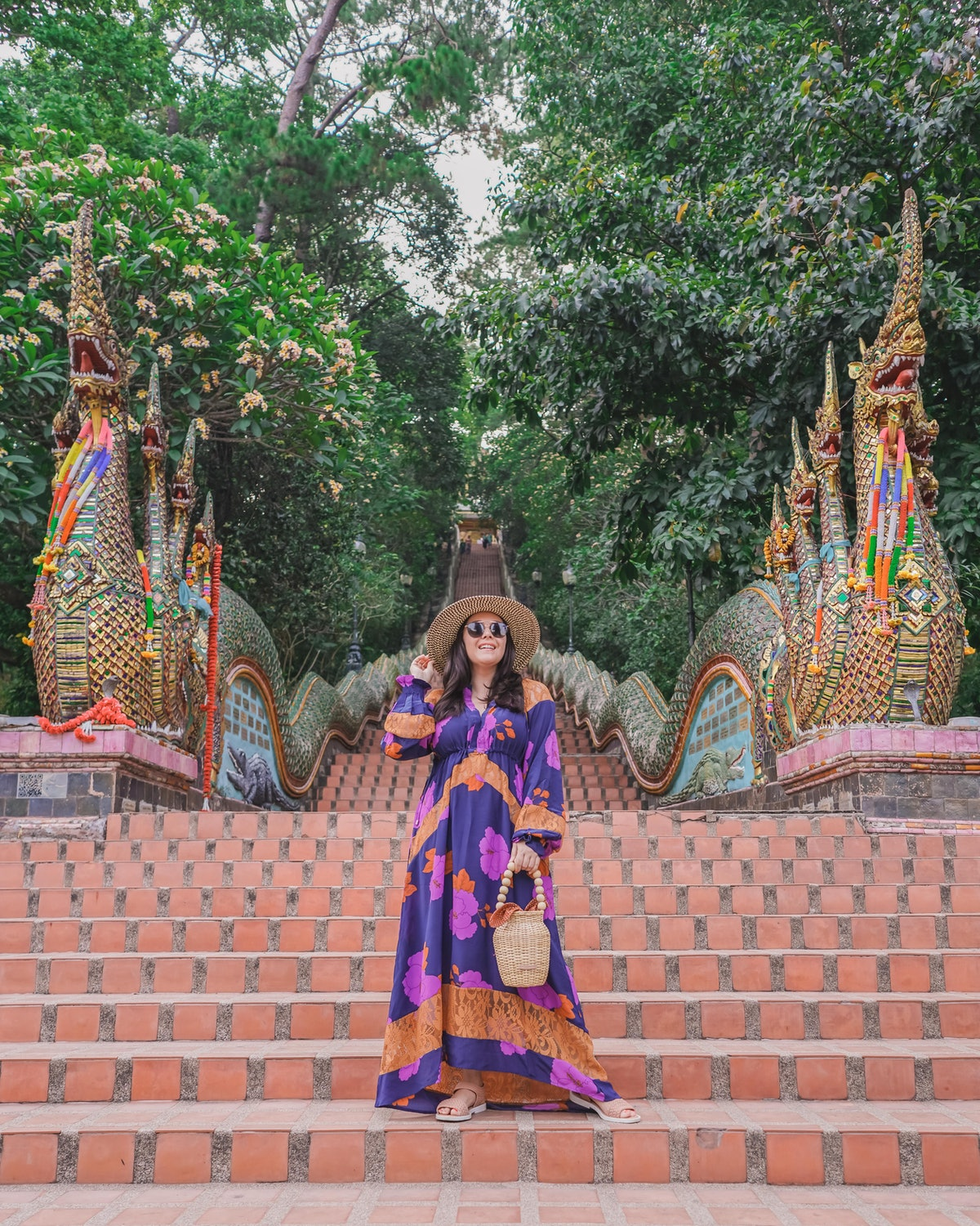 A woman in a colorful maxi dress and big sun hat poses on temple stairs in Thailand.