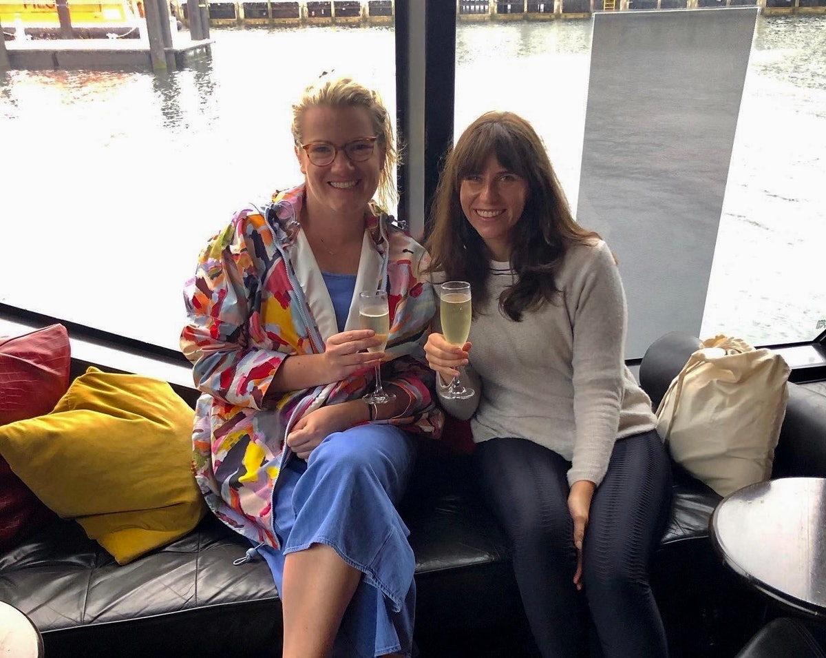 Two women sit on a boat with their champagne flutes.