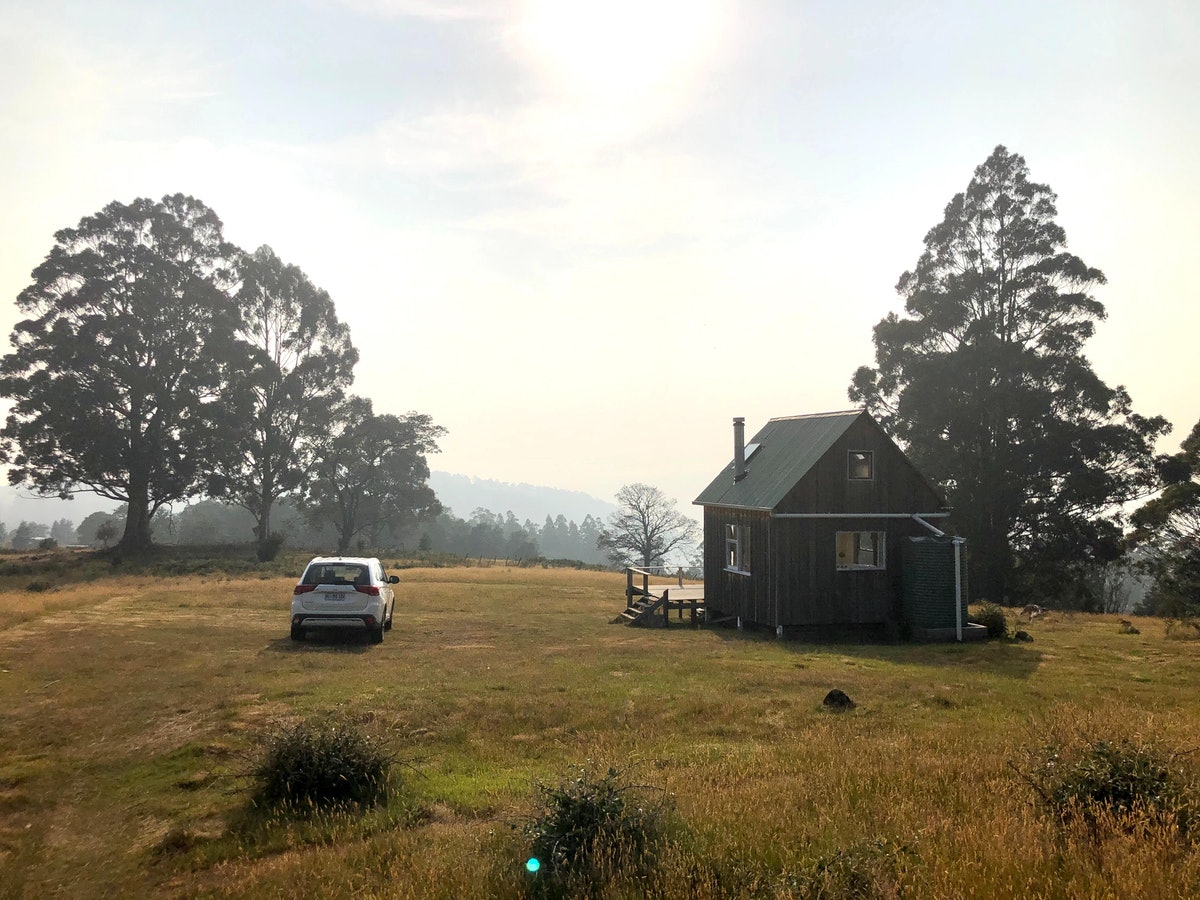A tiny home is located in a field with the sun shining over it.