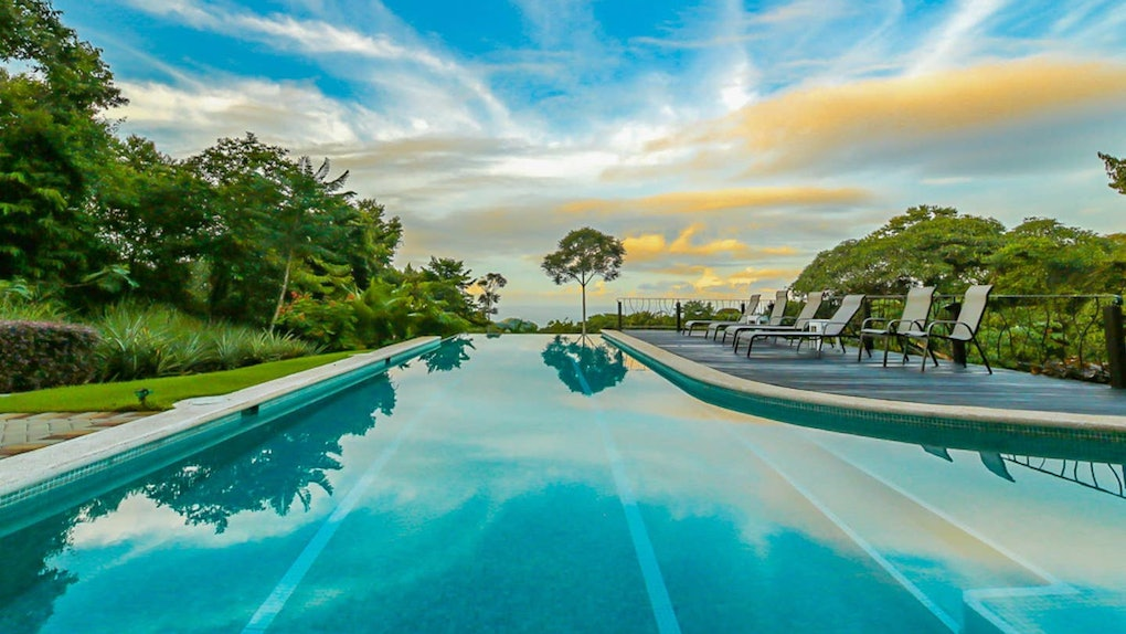 An airbnb in Costa Rica has an infinity lap pool surrounded by trees and bushes.