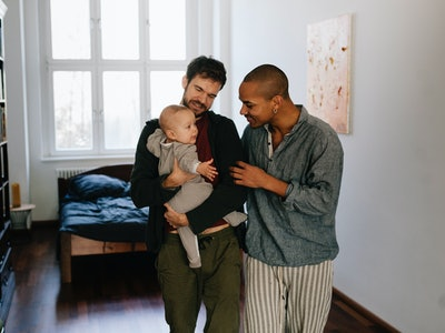 Two dads cuddle a baby