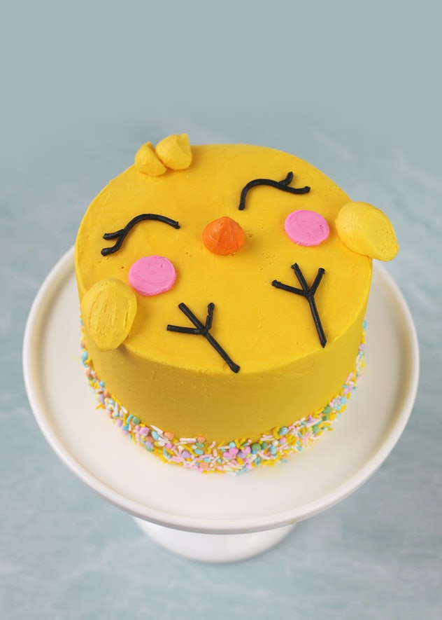 Cake decorated to look like a cartoon chick on a white cake stand
