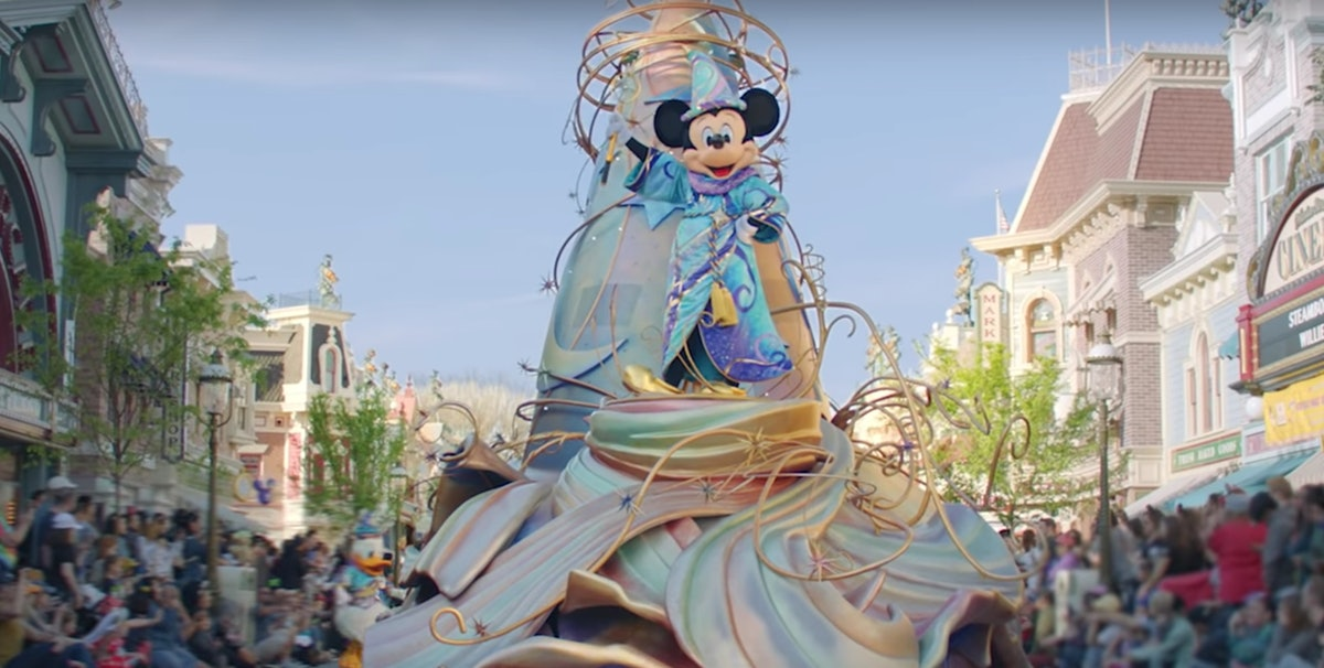 Mickey Mouse stands on top of a float in a Disney parade going down Main Street.