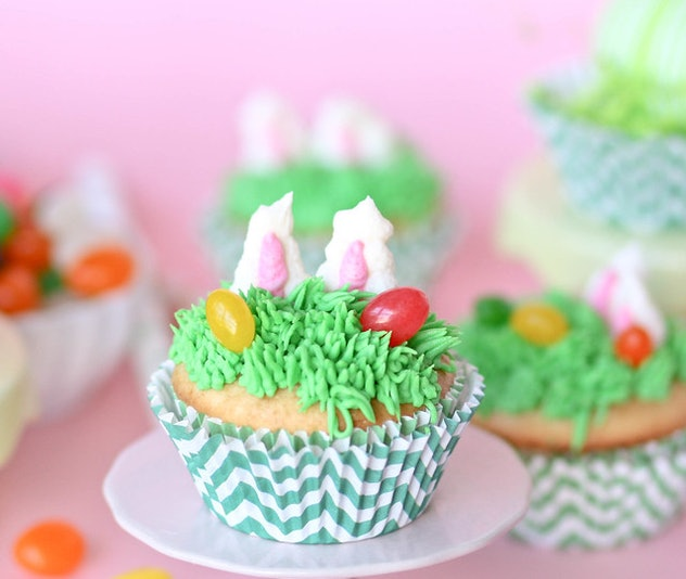 """Cupcake on a plate decorated with icing """"grass"""", jelly beans, and bunny ears popping up"""