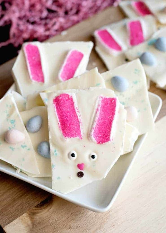 A plate of broken up pieces of white bark with easter candy and bunny faces in it