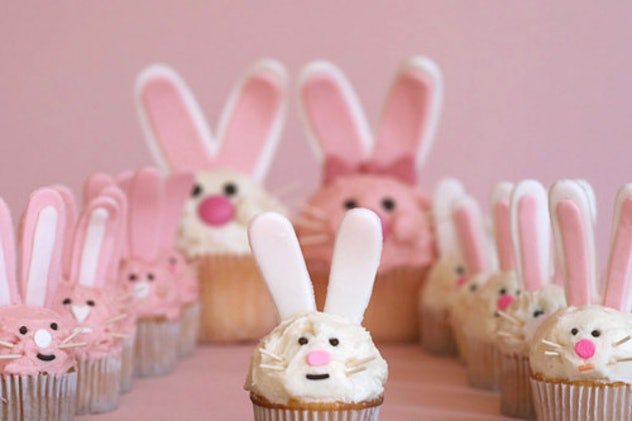 Several cupcakes with pink or white frosting and decoration to look like bunny faces