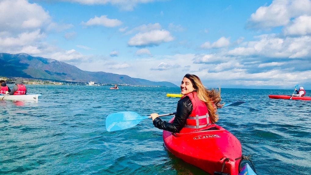 A woman in a red kayak smiles while on Lake Biwa in Japan.