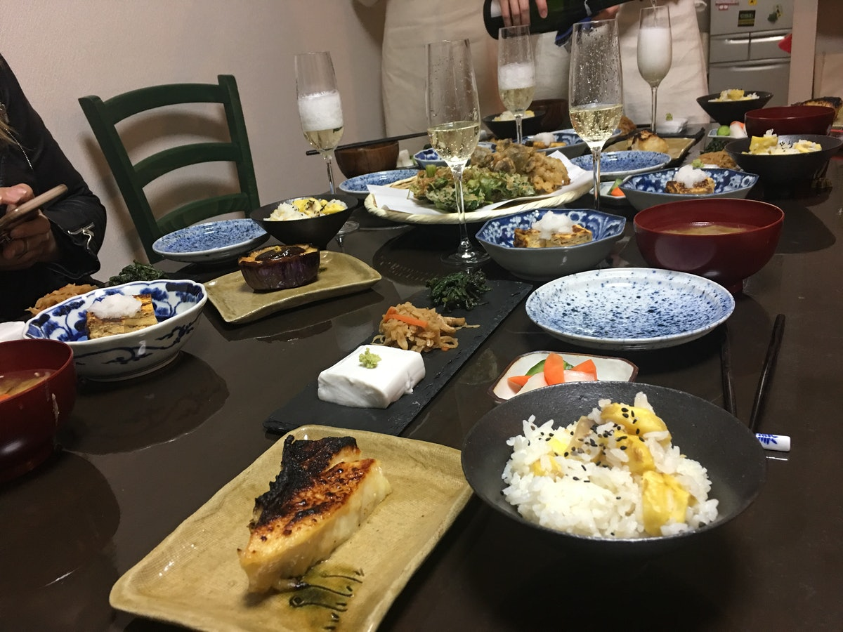 A table is filled with plates of food and flutes of champagne in Kyoto, Japan.