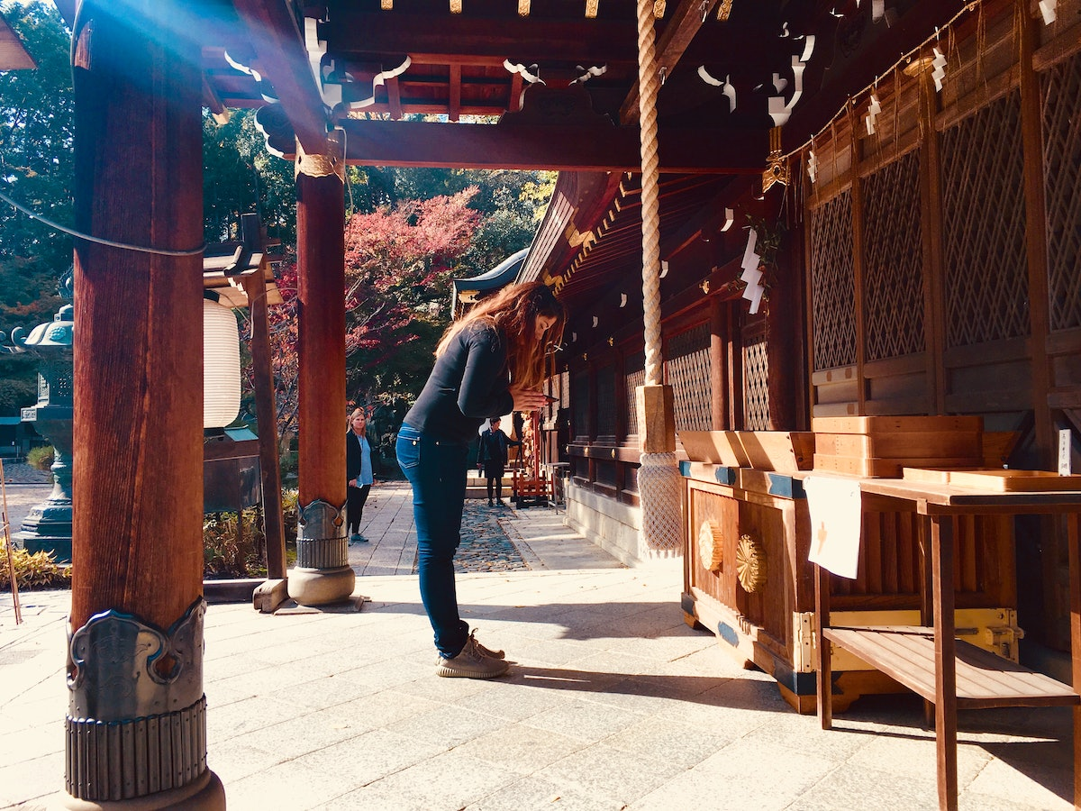 A woman bows in Kyoto, Japan on a sunny afternoon.