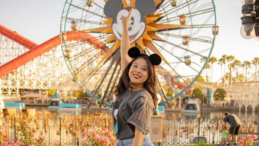 A woman wearing Mickey Mouse ears jumps up in the air in front of the Ferris wheel at Disneyland.