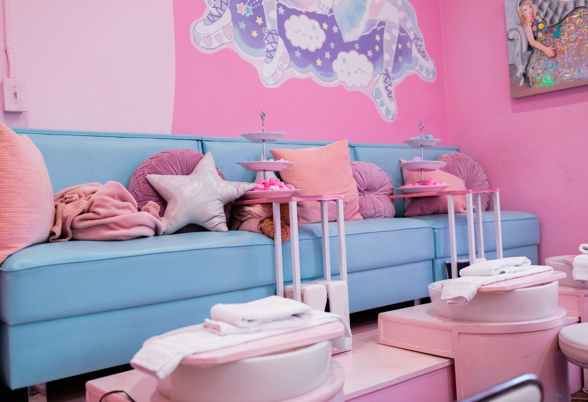 The interior of Cute Nail Studio in Austin, TX features a blue couch, pink walls, and lots of pink pillows at the pedicure station.