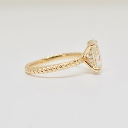 OVAL BRILLIANT IN A FRENCH PAVÉ HIDDEN HALO ROPED CABLE ENGAGEMENT RING IN YELLOW
