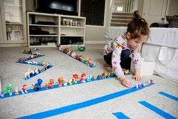 A child lines up toy animals on tape