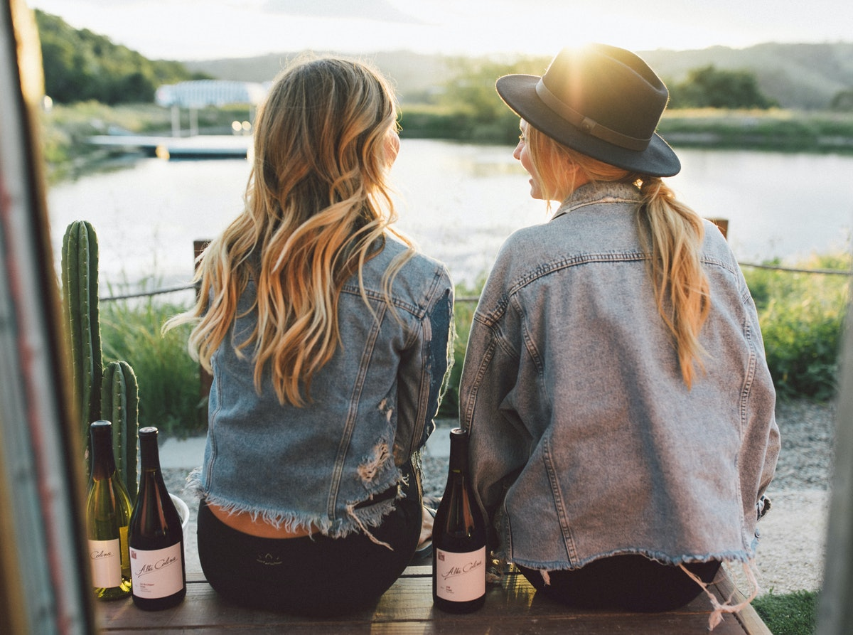 Two best friends sit on the dock at the Trailer Pond at Alta Colina Vineyard with bottles of wine.