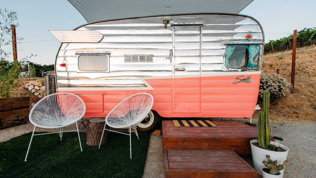 A pink and white vintage trailer at the Trailer Pond at Alta Colina Vineyard features outdoor seating and desert-like decor.