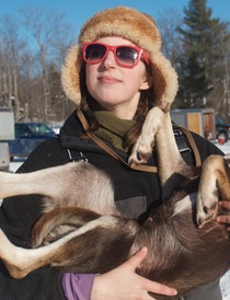 Blair Braverman, dogsled musher, holds one of her sled dogs for a photo