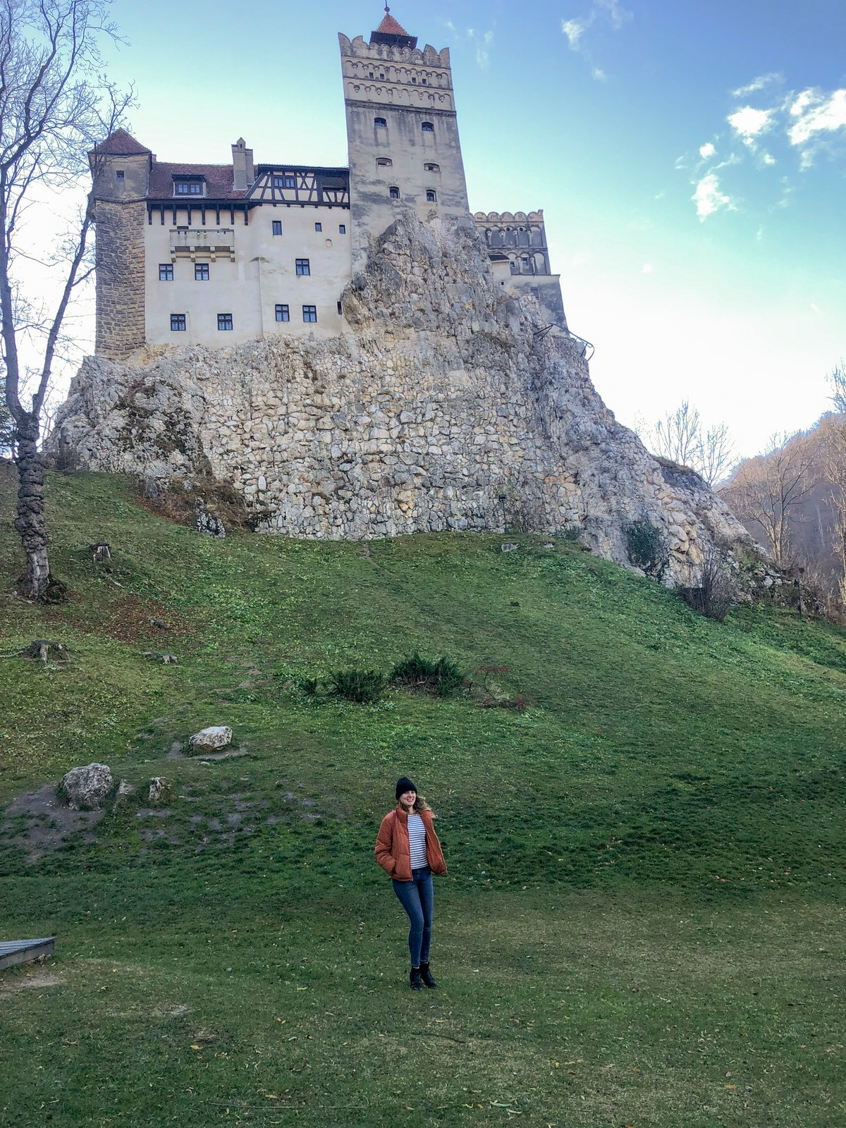 A woman wearing a puffer jacket, jeans, beanie cap, and booties poses on the grass in front of a hilltop castle in Romania.
