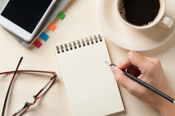 Young man right hand writing on blank notebook on wood table with coffee cup, smartphone, and glasse...
