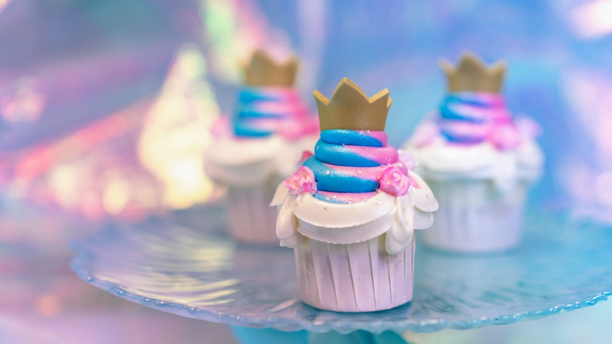 A pink and blue cupcake with a gold crown sits on a cupcake tray.