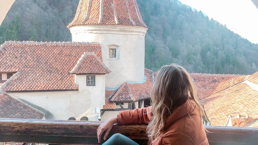 A woman wearing an orange jacket, jeans, and boots sits on a bench overlooking a castle.