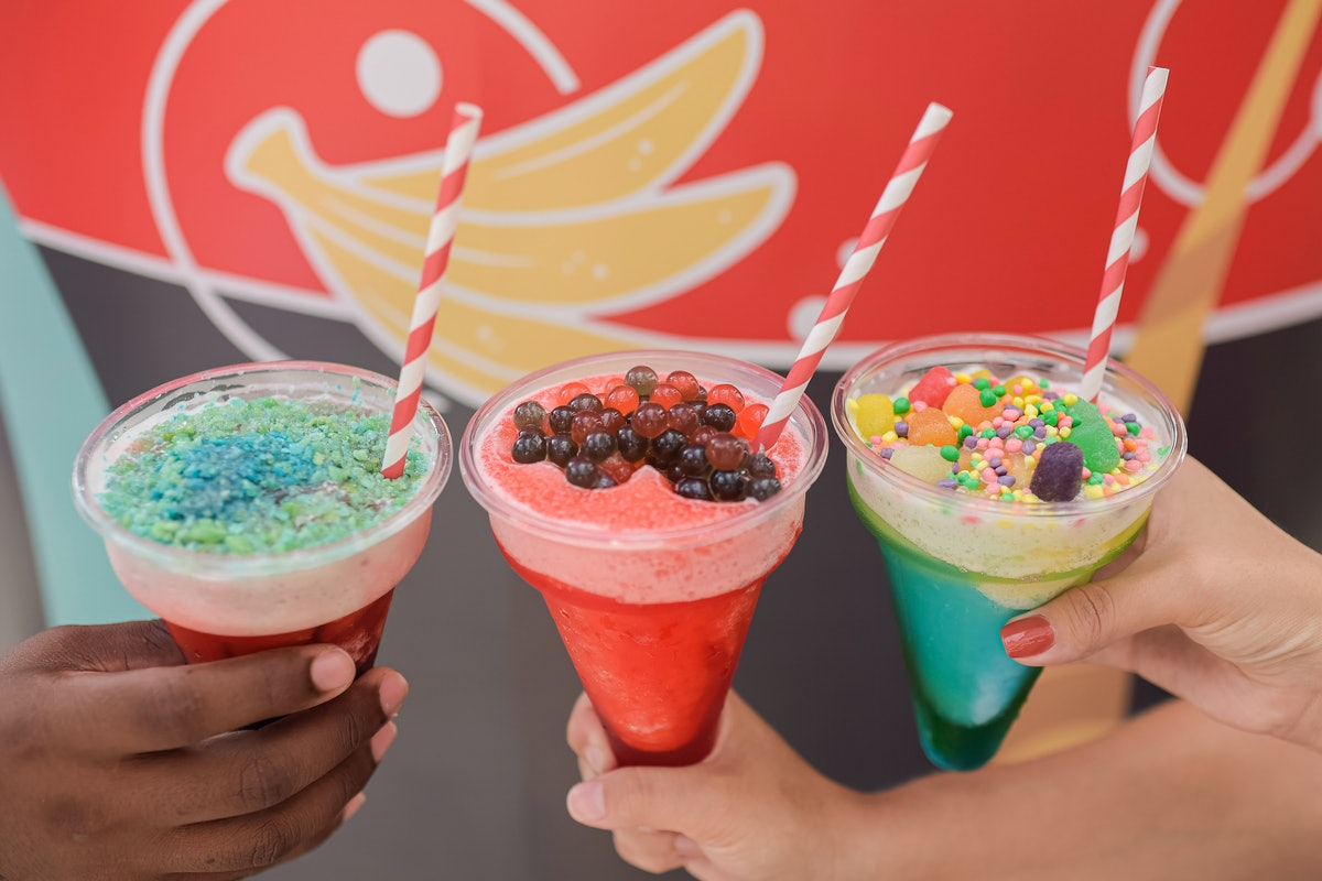 Three women's hands hold out colorful slushies in plastic cones, which are served at the 2020 Epcot International Flower & Garden Festival at Disney.