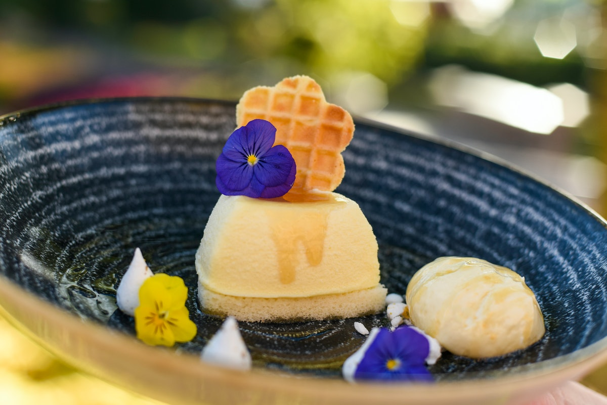 Purple and yellow flowers decorate a honey-mascarpone cheesecake, which is served at the 2020 Epcot International Flower & Garden Festival at Disney.