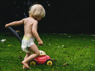 Child wearing diaper pushes a toy lawnmower