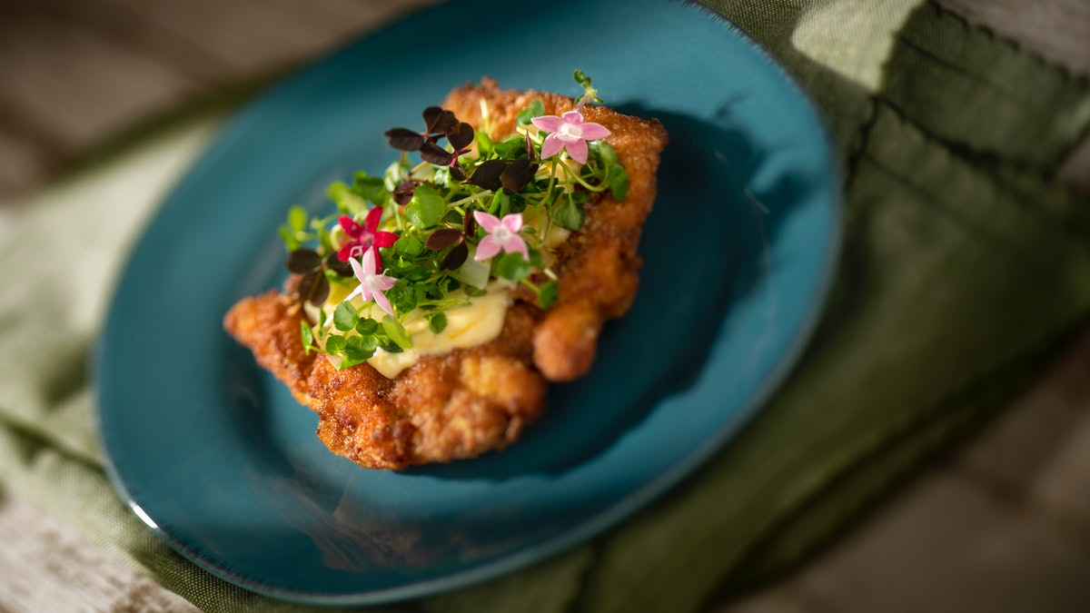 Flowers and greens decorate a citrus crispy chicken dish, which is served at the 2020 Epcot International Flower & Garden Festival at Disney.