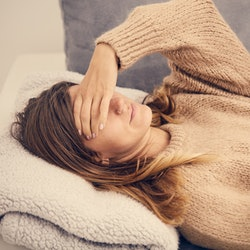 A woman lies on her couch trying to tell if she has a fever without a thermometer.
