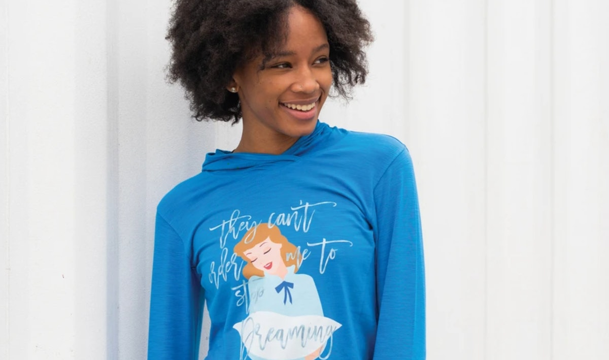 A woman wearing a 'Cinderella' blue hoodie, stands in front of a white wall.