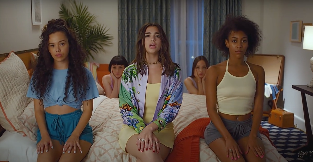 """Dua Lipa's music video for """"New Rules"""" features women sitting in colorful outfits on a hotel bed."""
