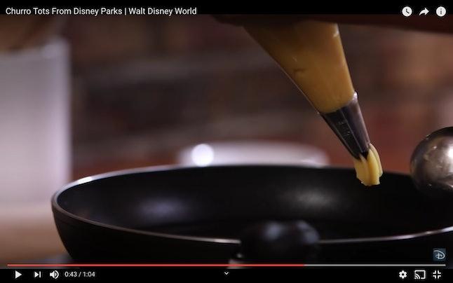 Next in the Disney churro bites recipe, pipe the churros into a saucepan.