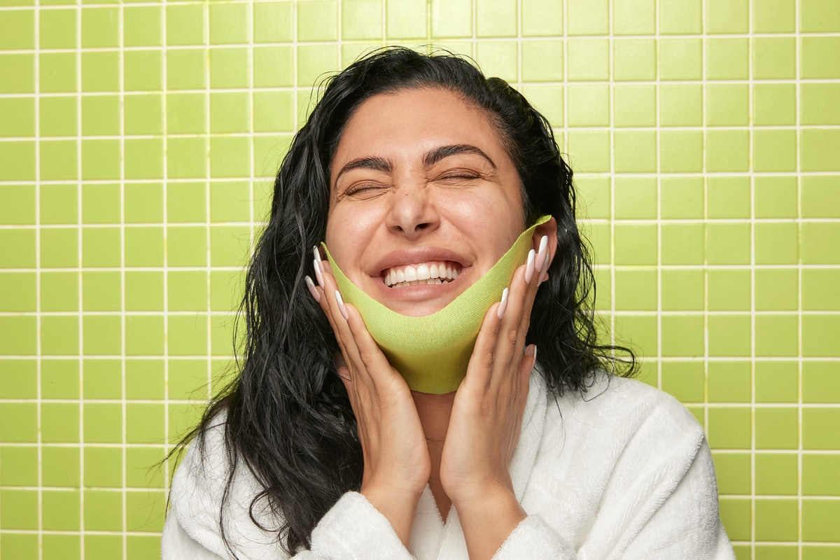 Huda Kattan wears Wishful's New Chin Lift Sculpting Sheet Mask made to define your chin
