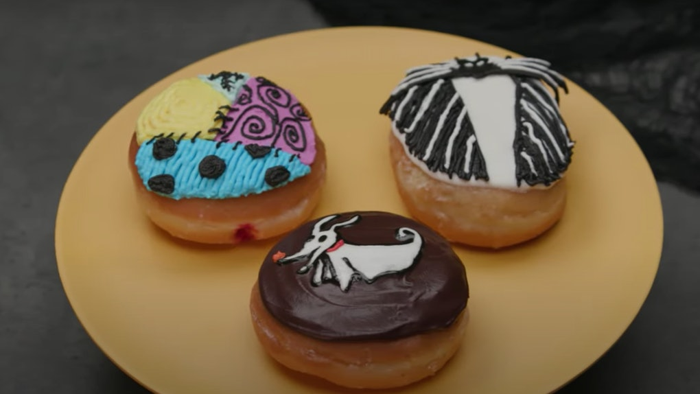 Three doughnuts decorated to look like characters from 'The Nightmare Before Christmas' are placed on a yellow plate.