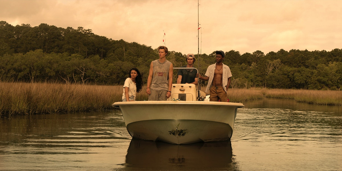 """The teens of Netflix's """"Outer Bank""""' cruise in the water on a boat"""